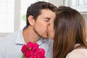 Close-up of a loving young couple kissing with flowers in hand at home