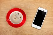 Mobile phone and coffee cup on office wooden table