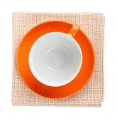 Orange coffee cup over kitchen towel. View from above. Isolated on white background