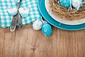 Easter eggs nest on plate over wooden background with copy space