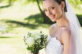 Closeup portrait of smiling bride with flower bouquet in garden