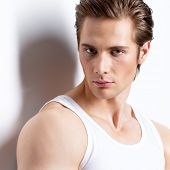Closeup fashion portrait of handsome young man in white shirt poses at studio over wall with contras