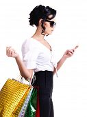 Portrait of a woman in glasses with shopping bags and mobile phone - isolated on white.