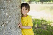 Portrait of a cheerful young boy standing by tree at the park