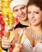 Young couple with champagne isolated on christmas decorated background