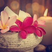 Spa still life setting with aromatic candles, frangipani flower, cold and hot stones in vintage retr