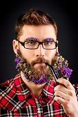 Handsome young man in spectacles and a beard of flowers smoking a pipe.