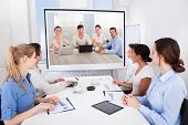 foto of training room  - Businesspeople Sitting In Conference Room Looking At Projector Screen - JPG