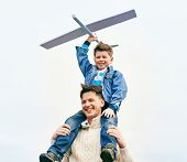 Photo of happy boy with toy airplane and his father looking at camera while playing outside