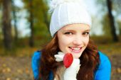 image of teenage girl  - beautiful happy girl with a red leaf in her mouth in the park - JPG