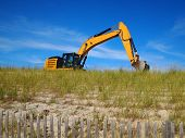 pic of dune grass  - A bulldozer works among the beach grasses atop a sand dune on a sunny day with a bright blue sky.