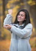 stock photo of tennis elbow  - Young woman with elbow pain outdoors in autumn - JPG