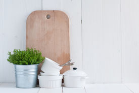 stock photo of paint pot  - Cottage life country kitchen decoration: a house plant in a metal pot with kitchen pottery utensils and napkins on white painted board. 