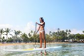 foto of hawaiian girl  - Hawaii beach lifestyle woman paddleboarding in bikini - JPG