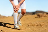 Постер, плакат: Running injury Male runner with knee pain Trail runner injured jogging in nature clutching his kn