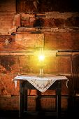 picture of kerosene lamp  - Burning Oil Lamp on the Aged Wooden Table in the Vintage Cabin Scenery - JPG