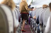 image of air hostess  - Interior of airplane with passengers on seats and stewardess walking the aisle - JPG
