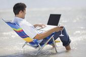 foto of telecommuting  - Hispanic man in beach chair with laptop - JPG