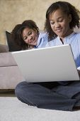 stock photo of identical twin girls  - African twin sisters looking at laptop - JPG