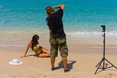 stock photo of bimbo  - Photographer Photoshoot on the beach with beautiful bikini model - JPG