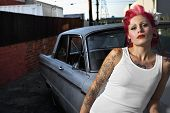stock photo of hispanic  - Tattooed Hispanic woman leaning on car - JPG