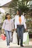 stock photo of chums  - African teenaged girls carrying shopping bags - JPG