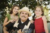 foto of niece  - Hispanic father playing guitar for daughters - JPG