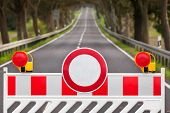 picture of safety barrier  - Red and white colored street barrier at an empty road - JPG
