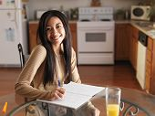picture of homework  - african teen girl posing with homework on kitchen table - JPG
