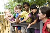 stock photo of daycare  - Diverse group of preschool 5 year old children playing in daycare with teacher - JPG