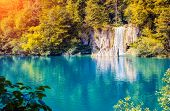 stock photo of waterfalls  - Majestic view on waterfall with turquoise water and sunny beams in Plitvice Lakes National Park - JPG