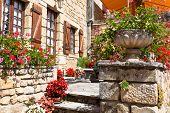 foto of stone house  - Bright flower pots on an ancient stone house porch in Southern France