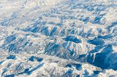 stock photo of snow capped mountains  - Aerial view of snow capped High Alps mountains in winter Switzerland - JPG