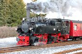 stock photo of wagon  - A steam locomotive travels with people wagons on railroad tracks - JPG