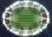 pic of football pitch  - A football stadium with posts on a marked green grass pitch in the night time illuminated by an array of spotlights - JPG