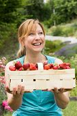 picture of strawberry blonde  - A smiling woman holds a basket filled with fresh strawberries
