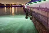 image of sewage  - Sewage pipe discharging water into a river at night - JPG