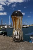 stock photo of bollard  - Weathered Timber Bollard with a Steel Cap that is Rusted and causing Rust stains to run down the White Bollard.