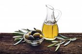 image of kalamata olives  - Glass bottle of premium virgin olive oil and some olives with leaves on wooden background isolated - JPG