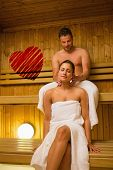 stock photo of sauna  - Man giving his girlfriend a neck massage in sauna against red heart - JPG