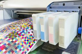 stock photo of cartridge  - large format ink jet printer cartridge with color managament target paper roll - JPG