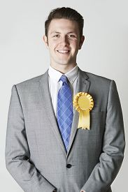 image of politician  - Portrait Of Smiling Politician Wearing Yellow Rosette - JPG