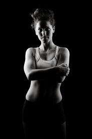 stock photo of athletic woman  - Low key fitness woman monochrome on black background - JPG