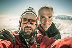 picture of italian alps  - Adult european men taking selfie on the mountain summit with snowcapped italian Alps in background - JPG