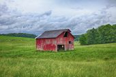 picture of red barn  - A classic red barn stands along in the grassy hills of a farm in Eastern Ohilo - JPG