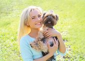 picture of yorkshire terrier  - Portrait of happy young woman owner with yorkshire terrier dog in the park - JPG