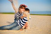 stock photo of little sister  - Portrait of happy teen sister and little brother on the beach - JPG