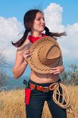 girl cowboy in the field with  hat on  chest