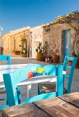 foto of stone house  - Painted wooden chair in the main small square of the fishing village Marzamemi Sicily and some typical stone houses in the background - JPG