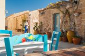 image of stone house  - Painted wooden chair in the main small square of the fishing village Marzamemi Sicily and some typical stone houses in the background  - JPG